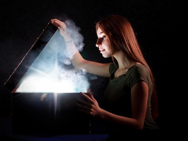 Симпатичная девушка открывает загадочную коробку с дымом и светом внутри