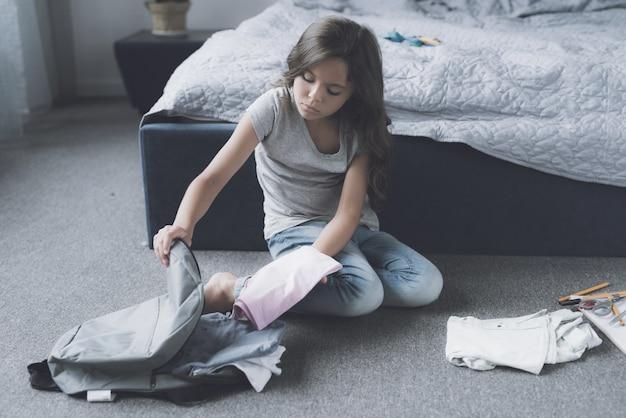 Cute girl packing bag sits on floor in bedroom