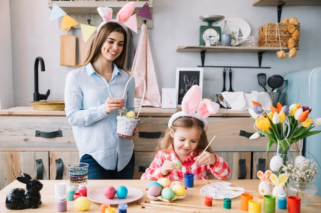 Cute girl painting eggs for easter near mother with basket