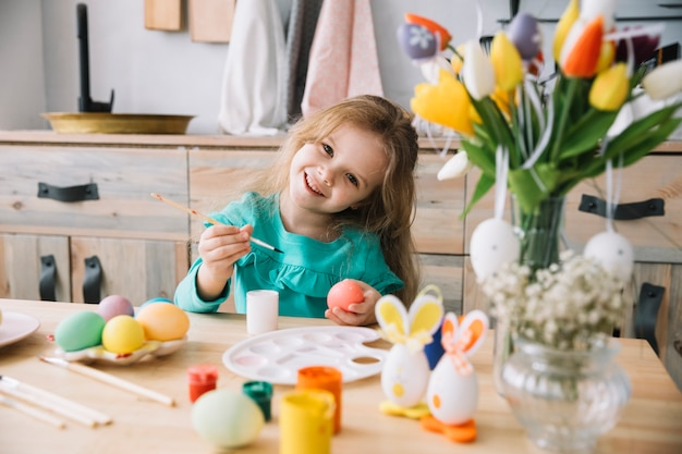 Cute girl painting eggs for easter at table