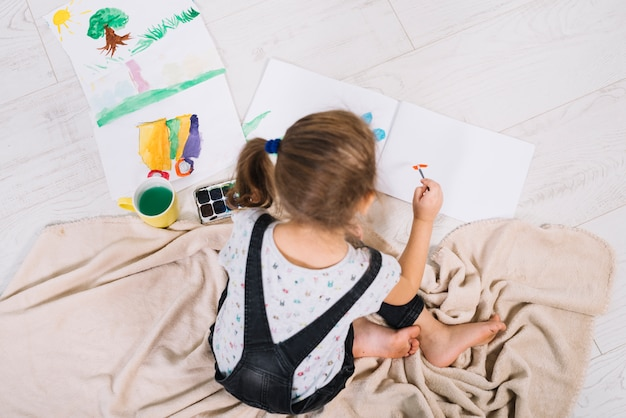 Cute girl painting with aquarelle on floor