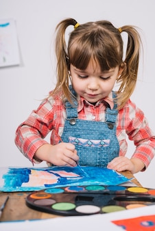 Cute girl painting with blue gouache at wooden table