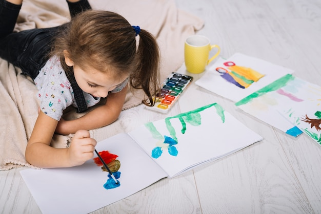 Cute girl painting with bright aquarelle on floor