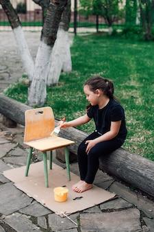 Милая девочка красит деревянный стул желтой краской - детское экологичное хобби