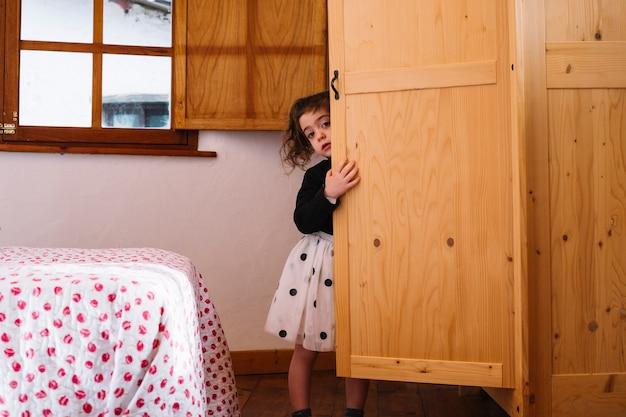 Симпатичная девушка, выглядывающая из деревянного шкафа