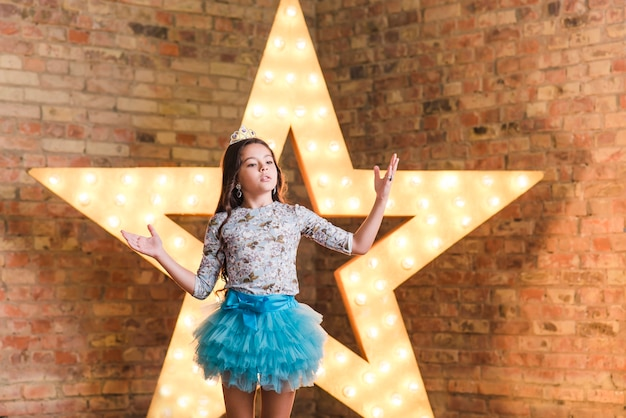 Cute girl performing in front of glowing star against brick wall