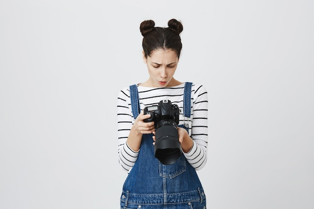 Cute girl photographer looking at camera screen, searching for perfect picture
