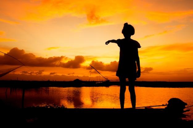 川の夕日を背景にかわいい女の子プレイ