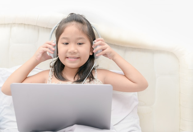 Cute girl play laptop and listening music
