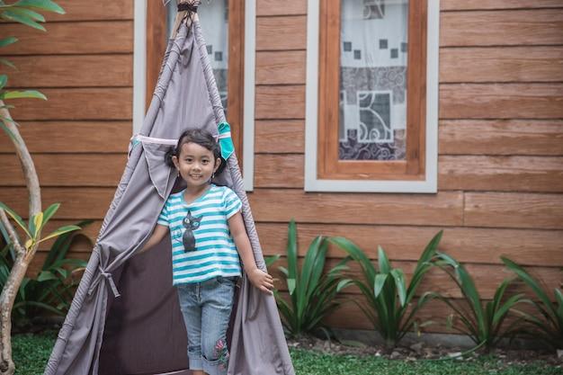 Милая девушка играет на заднем дворе