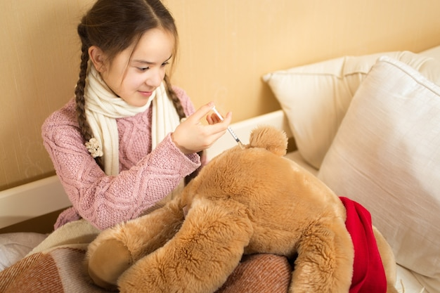 Cute girl playing with brown teddy bear and making injection