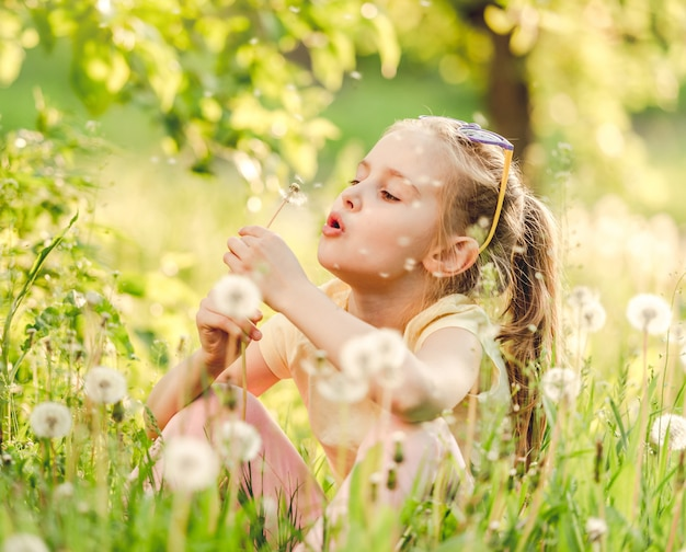 Cute girl playing with dandelions