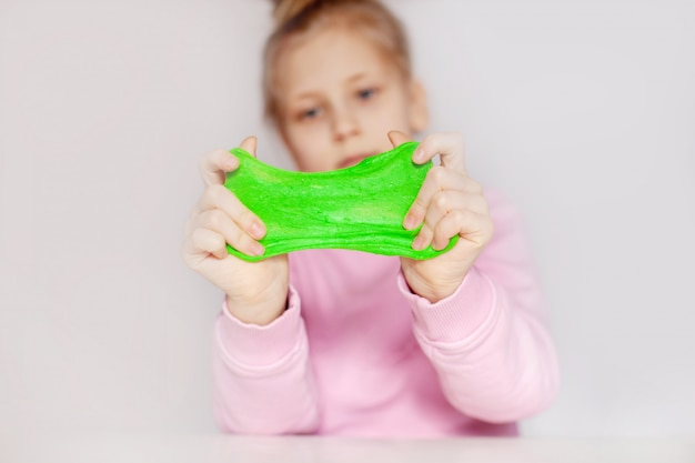 Cute girl playing with green slime