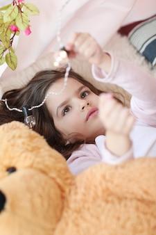 Милая девушка играет с лампочками с кровати