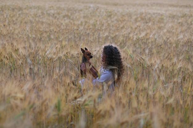 フィールドで子犬と遊ぶかわいい女の子