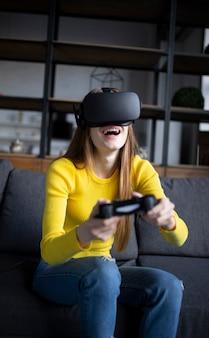 귀여운 소녀는 콘솔에서 게임을 재생합니다. 가상 현실 헤드셋을 사용하여 행복 한 젊은 여자
