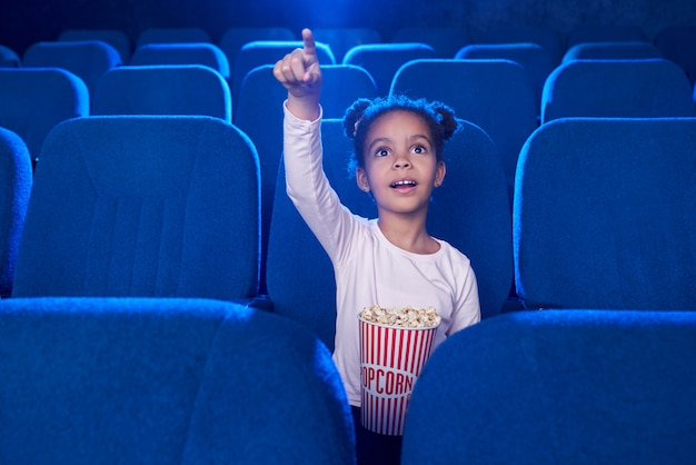 Cute girl poiniting with finger at screen in cinema.