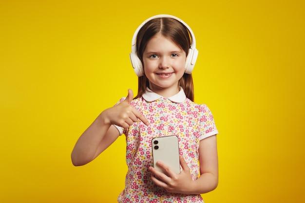 Симпатичная девушка указывает на мобильный телефон с белыми наушниками, подключенными к смартфону