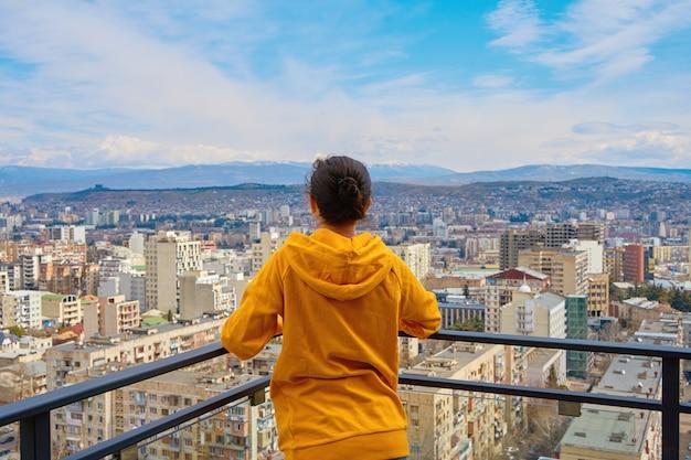 街並みを背後にした超高層ビルの高層ビルのバルコニーに立ってポーズをとるかわいい女の子。