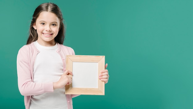 Cute girl posing with photo frame in studio