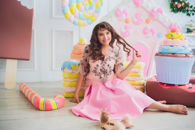 ピンクのドーナツでポーズ、浮気、デザート、悪い食べ物、ドーナツの穴を覗き、目でドーナツを保つかわいい女の子