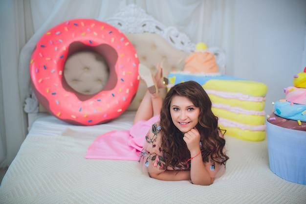 Милая девушка позирует с розовыми пончиками, дурачиться, десерт, плохая еда, смотрит в дырку от пончика, держит пончики на глазах