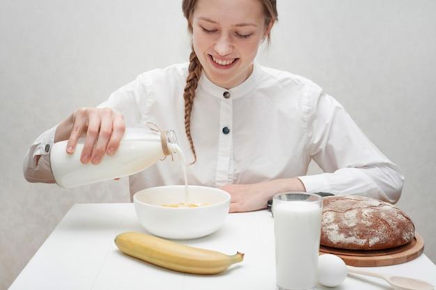 Милая девушка наливает молоко в миску