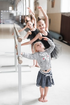 Cute girl practicing ballet dance with her sister in dance studio