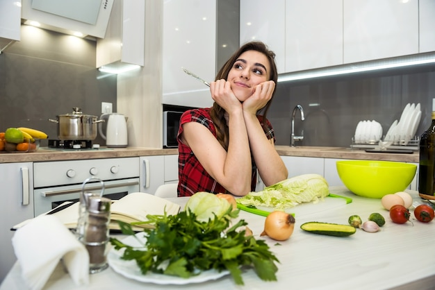 Cute girl prepares a salad of different vegetables and greens for a healthy lifestyle