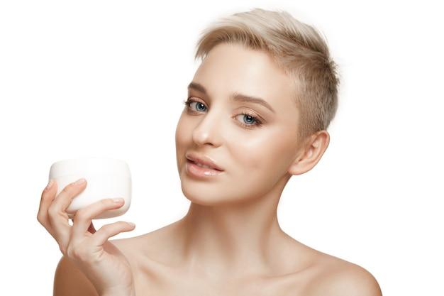 Cute girl preparing to start her day. she is applying moisturizer cream on face.