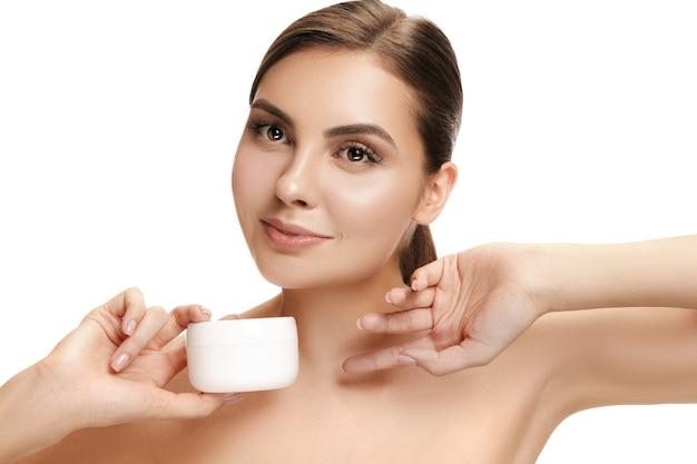 Cute girl preparing to start her day. she is applying moisturizer cream on face .