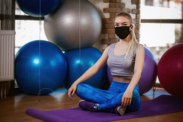 Cute girl in a protective mask sits in a lotus position on the rug. coronavirus (covid-19) protection concept.