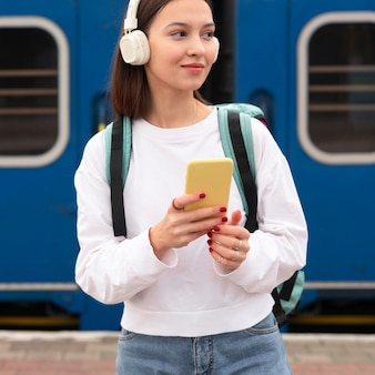 Cute girl at the railway station listening to music
