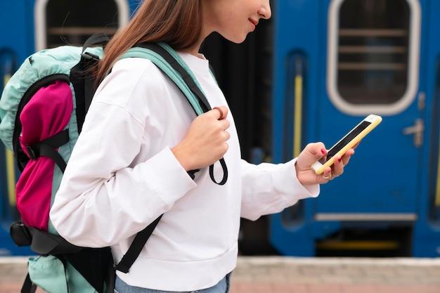 Ragazza carina alla stazione ferroviaria utilizzando il suo smartphone