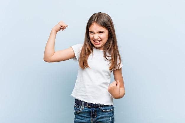 かわいい女の子が勝利、勝者の概念の後の拳を上げる。