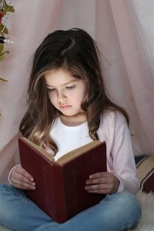 Милая девушка читает книгу вокруг милого украшения