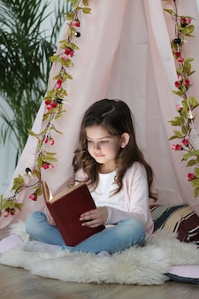 Cute girl reading a book around cute decoration