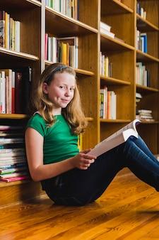 Cute girl reading book sitting on floor