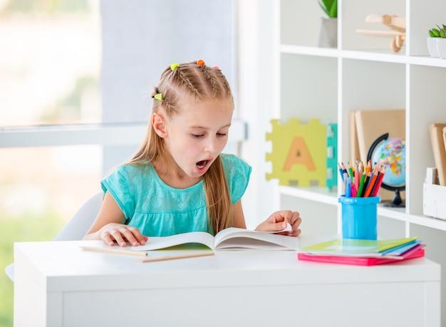 Cute girl reading books at schooldesk