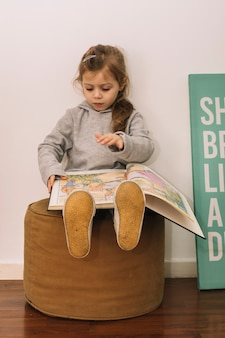 Cute girl reading on pouf