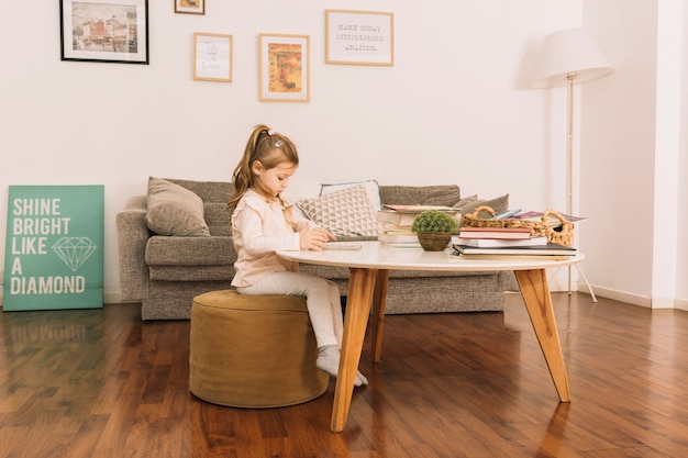 Cute girl reading at table