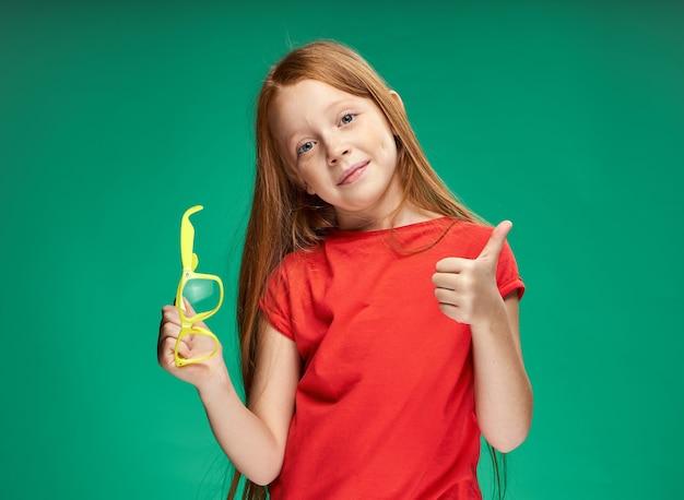 学校の緑の壁を学ぶかわいい女の子の赤い髪の感情