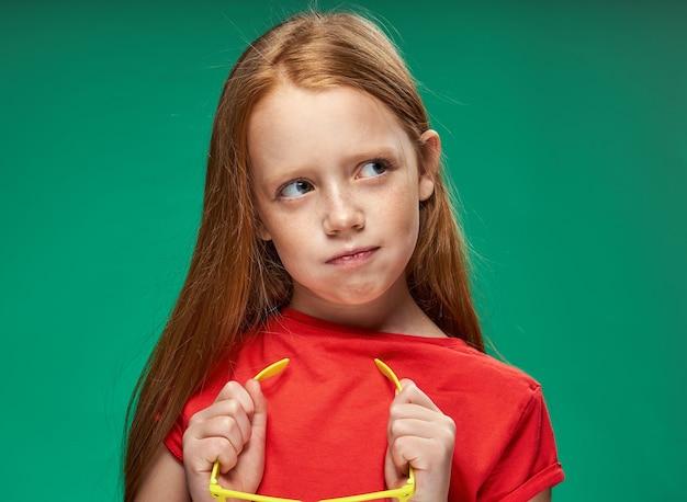 Милая девушка красные волосы жесты руками эмоции школа детства зеленый фон. фото высокого качества
