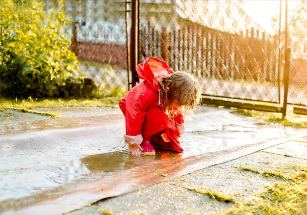 Cute girl in a red jacket is jumping in the puddle.the setting warm summer or autumn sun. summer in the village.