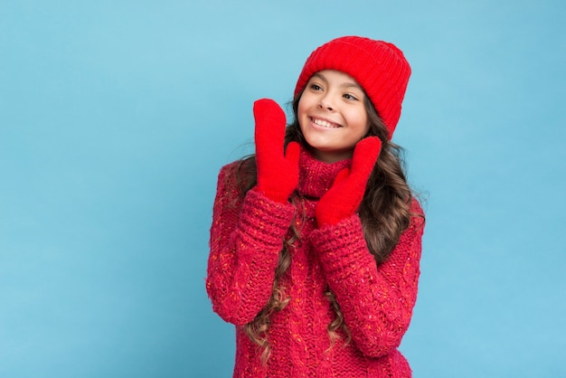 Cute girl in red winter clothes