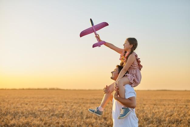 아버지의 어깨를 타고 밀밭에서 하늘을 배경으로 장난감 비행기를 가지고 노는 귀여운 소녀
