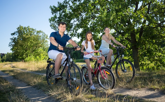 Cute girl riding with parents on bicycles in meadow at sunny day. concept of family sport