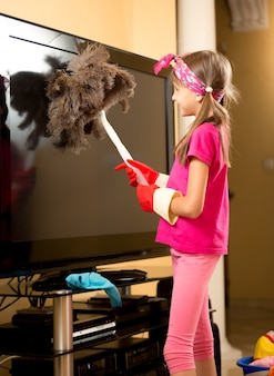 Cute girl in rubber gloves cleaning big tv from dust with brush