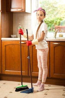 Cute girl in rubber gloves sweeping floor at kitchen with swab and scoop