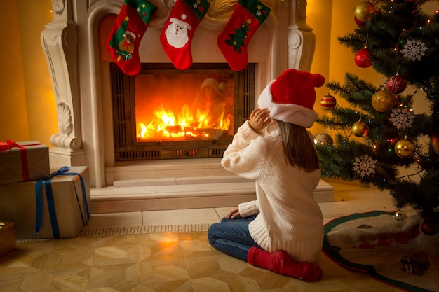 Cute girl in santa hat sitting on floor under christmas tree and looking at burning fireplace